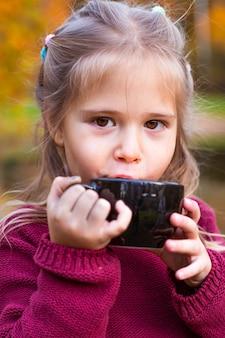 Enfants dans la forêt d'automne sur un pique-nique en buvant du thé