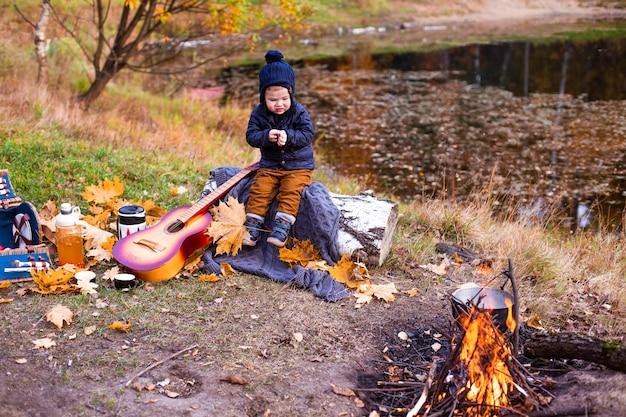 Enfants dans la forêt d'automne sur un pique-nique grill saucisses et jouer de la guitare