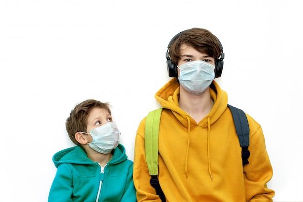 Enfants dans des masques médicaux dans des vêtements lumineux, isolés, copiez l'espace. protection contre le coronavirus