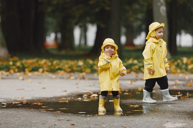 Enfants dans un parc d'automne. les enfants dans un imperméable jaune. les gens s'amusent à l'extérieur.