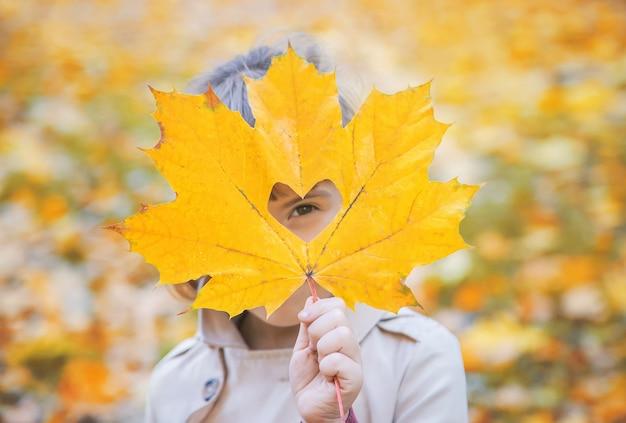 Enfants dans le parc avec des feuilles d'automne. mise au point sélective.