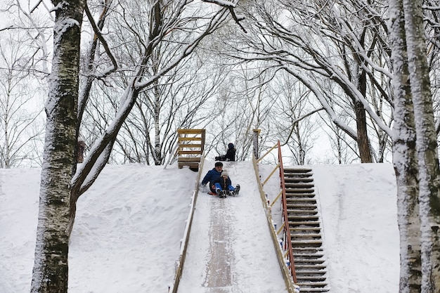 Enfants dans le parc en hiver. les enfants jouent avec de la neige sur l'aire de jeux. ils sculptent des bonhommes de neige et dévalent les collines.
