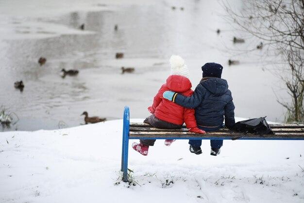 Les enfants dans le parc d'hiver jouent avec la neige