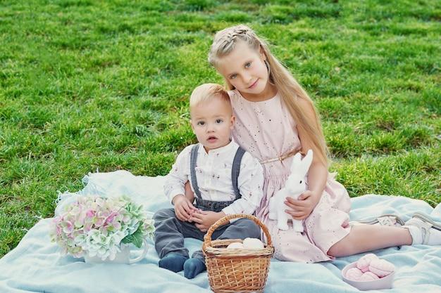 Enfants dans le parc sur pique-nique de pâques avec des oeufs et un lapin