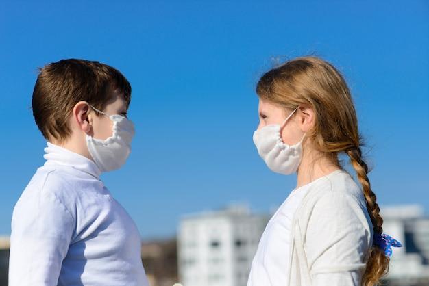Enfants dans un parc de la ville dans un masque médical. marcher dans la rue pendant la période de quarantaine de la pandémie de coronavirus dans le monde. précautions et enseignement aux enfants