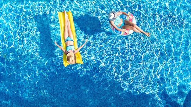 Enfants dans la piscine vue aérienne du drone fom ci-dessus, les enfants heureux nagent sur l'anneau gonflable et le matelas, les filles actives s'amusent dans l'eau en vacances en famille sur le lieu de vacances