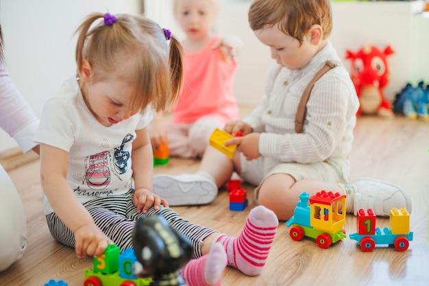 Les enfants dans la salle de jeux sur le sol