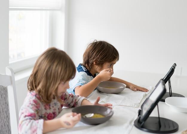 Enfants dans la salle à manger manger et regarder une tablette