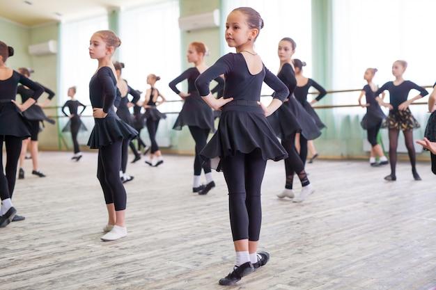 Les enfants dansent avec un entraîneur dans une grande salle de formation.