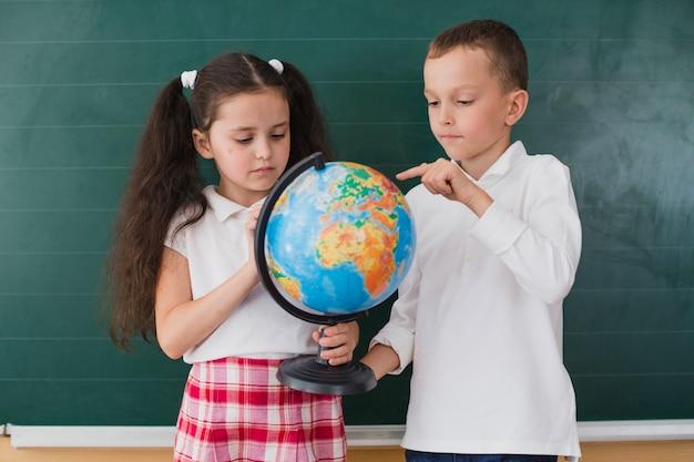 Enfants debout avec globe