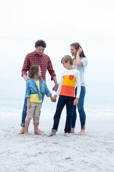Enfants debout avec les parents au bord de la mer