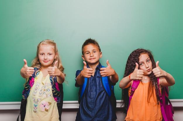 Les enfants debout avec le pouce vers le haut