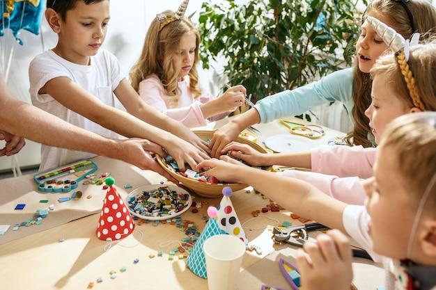 Enfants et décorations d'anniversaire. garçons et filles à table avec de la nourriture, des gâteaux, des boissons et des gadgets de fête.