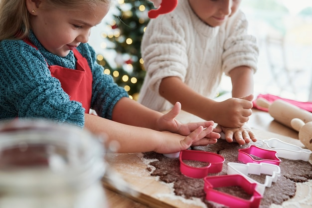 Enfants découpant des biscuits en pain d'épice