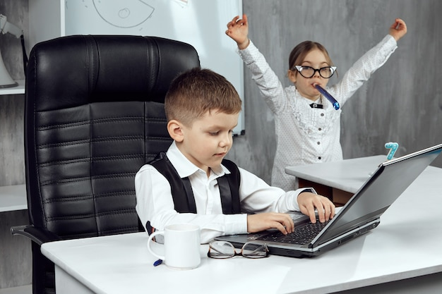 Des enfants déguisés en employés de bureau célèbrent le septième anniversaire de l'entreprise. les petits employés de bureau apprécient les vacances. le concept de vacances au travail. les enfants sont les patrons.