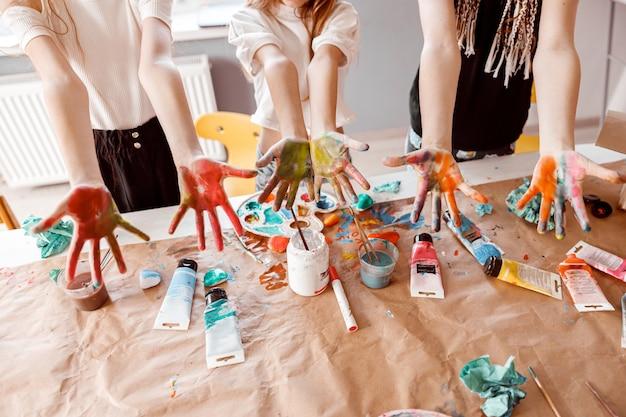 Enfants démontrant leurs paumes peintes à l'aquarelle