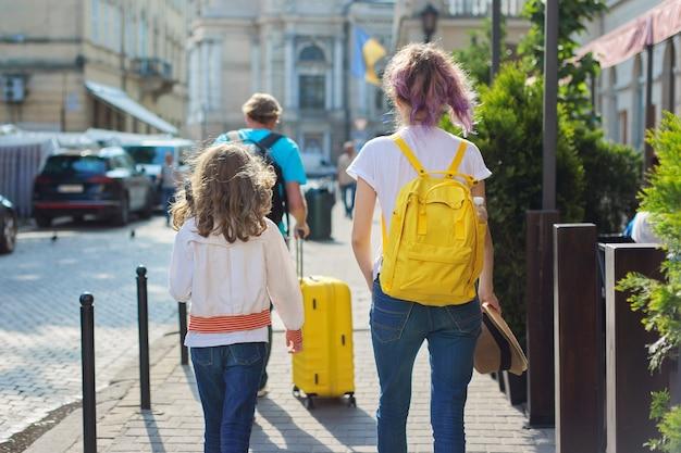 Enfants deux filles filles et père, touristes se promenant dans la ville avec des sacs à dos et une valise. voyage, famille, vacances, tourisme, concept d'été