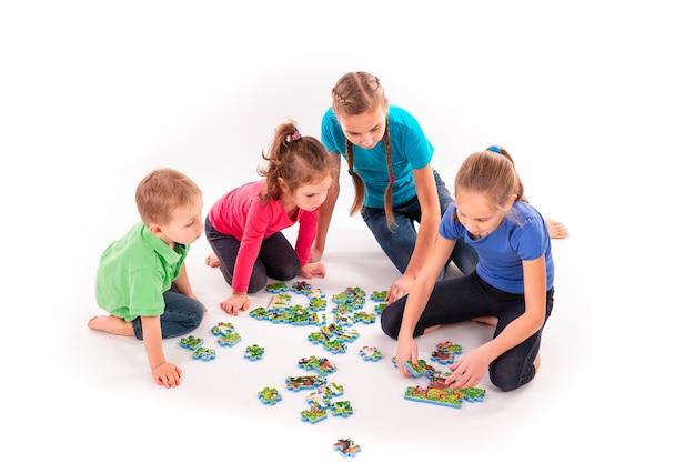 Les enfants de différents âges résolvent des puzzles ensemble. travail d'équipe, travailler ensemble, résoudre le concept de problèmes