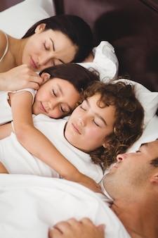 Enfants dormant avec leurs parents au lit