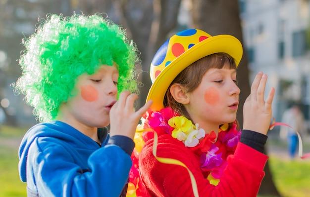 Enfants drôle de carnaval souriant et jouant en plein air