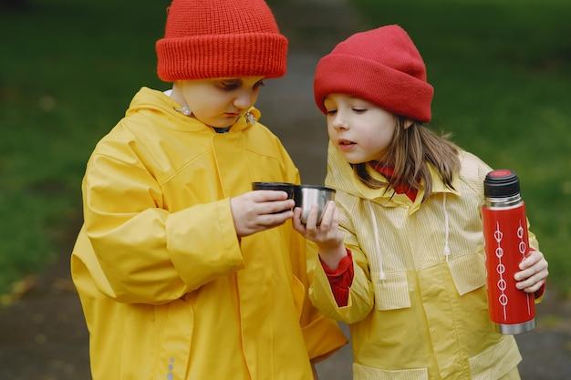 Enfants drôles en bottes de pluie jouant dans un parc pluvieux