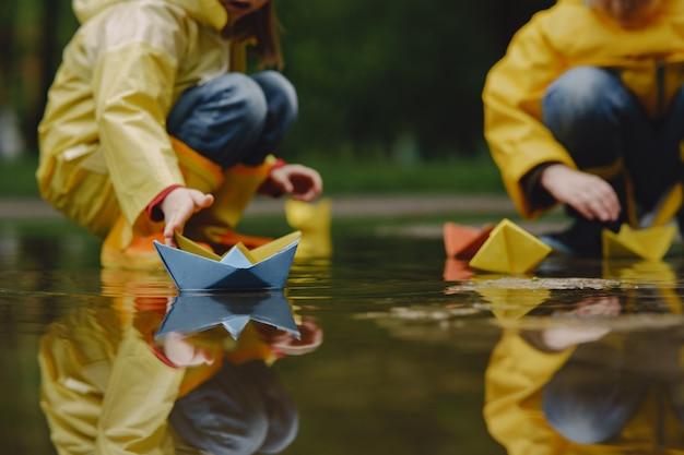 Enfants drôles en bottes de pluie jouant avec un navire en papier par une flaque d'eau