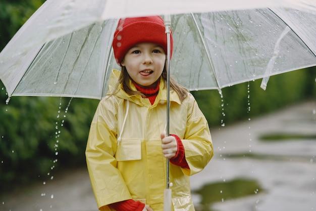 Enfants drôles dans des bottes de pluie jouant par une flaque d'eau