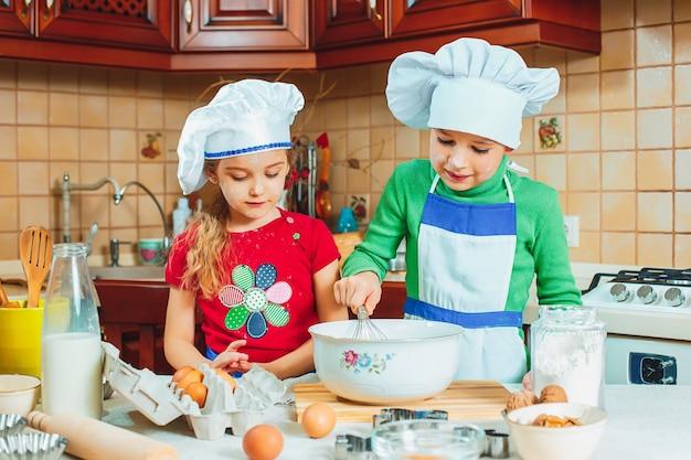 Les enfants drôles de famille heureuse préparent la pâte, cuisent des biscuits dans la cuisine