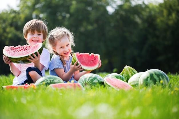 Enfants drôles mangeant la pastèque en plein air.