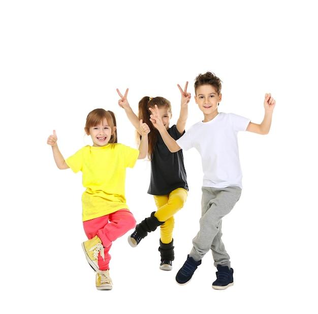 Enfants drôles mignons dansant sur une surface blanche