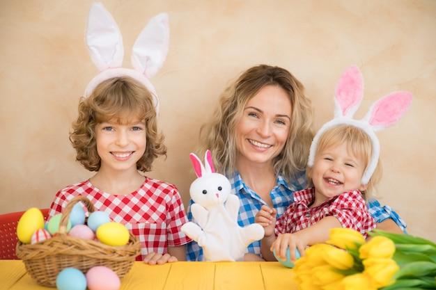 Enfants drôles portant le lapin de pâques. famille s'amuser à la maison