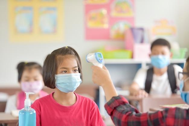 Les enfants de l'école avec un masque de protection contre le virus de la grippe à la leçon en classe