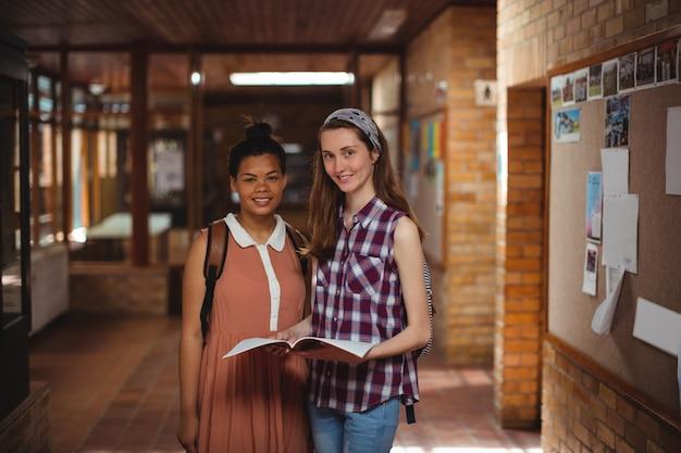 Les enfants de l'école tenant des livres dans le couloir à l'école