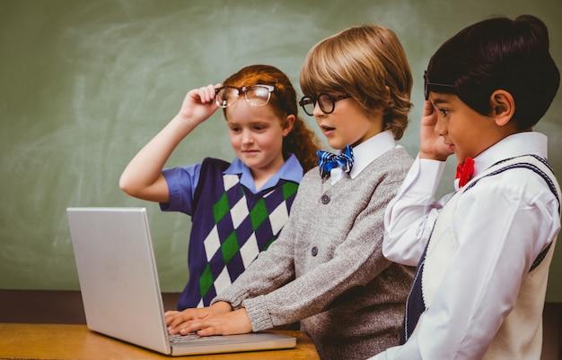 Enfants de l'école utilisant un ordinateur portable dans la classe