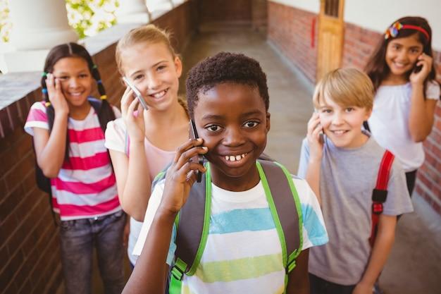 Enfants de l'école utilisant des téléphones cellulaires dans le couloir de l'école