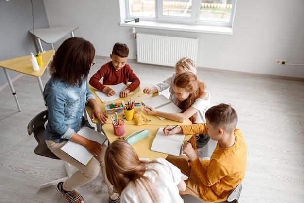 Enfants écrivant dans des cahiers assis à table avec le professeur