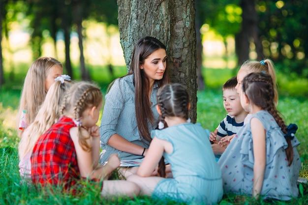 Enfants et éducation, jeune femme au travail en tant qu'éducatrice, livre de lecture pour garçons et filles dans le parc.