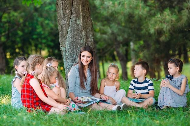 Enfants et éducation, jeune femme au travail en tant qu'éducatrice, livre de lecture pour garçons et filles dans un parc