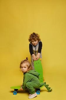 Enfants élégants dans des tenues modernes, petite fille et petit garçon en salopette posant avec des planches à roulettes sur le fond jaune, isolé. mode enfantine. sport de rue