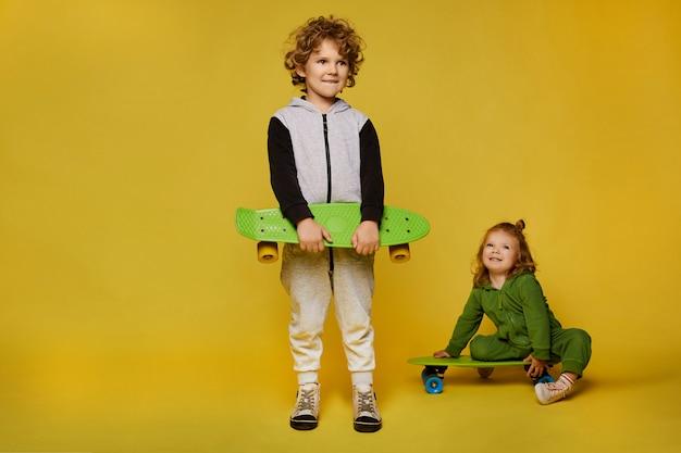 Enfants élégants dans des tenues modernes posant avec des planches à roulettes. petite fille et petit garçon isolé sur fond jaune avec espace de copie. mode enfantine