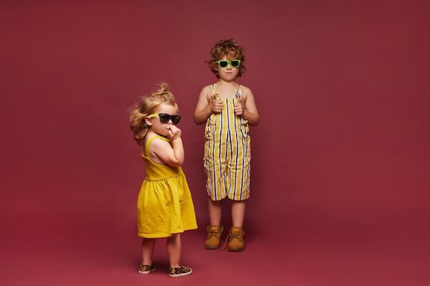 Enfants élégants mignons dans des vêtements à la mode posant sur fond rose. une petite fille dans une robe et des lunettes de soleil et un garçon dans une combinaison élégante d'été et des lunettes de soleil