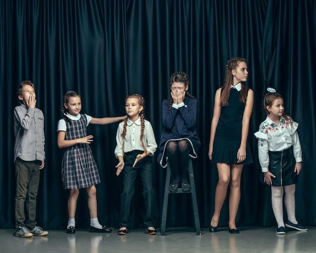 Enfants élégants mignons sur un espace sombre. les belles adolescentes et garçon debout ensemble
