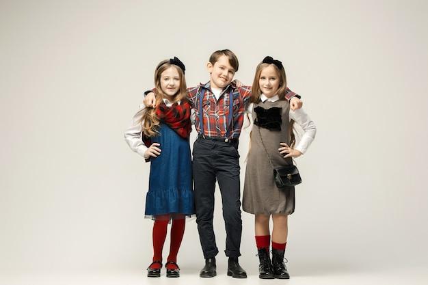 Enfants élégants mignons sur studio blanc