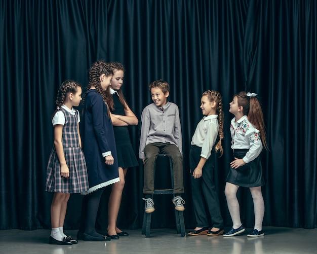 Enfants élégants mignons sur studio sombre. les belles adolescentes et garçon debout ensemble
