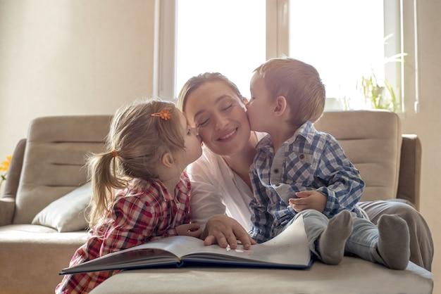 Enfants embrassant leur heureuse mère pendant qu'elle lit un livre