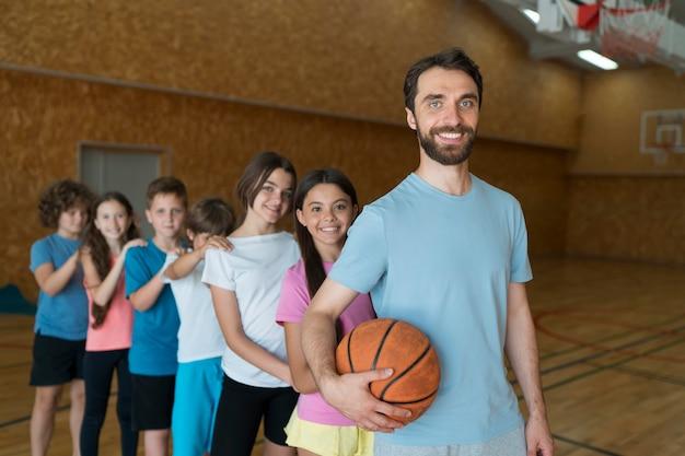 Enfants et enseignant de tir moyen avec ballon de basket