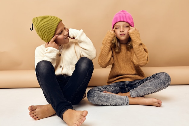 Enfants ensemble dans des chapeaux multicolores amusants vêtements décontractés fond isolé