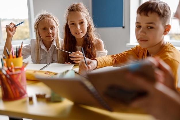 Enfants étudiant à l'école et assis à la table