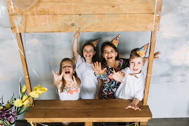 Des enfants excités qui étendent leurs bras lors d'une fête d'anniversaire