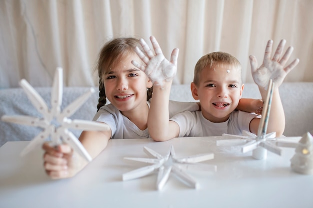 Les enfants fabriquent des flocons de neige de noël à partir d'une pince à linge réutilisable ornement original bricolage décoration du nouvel an